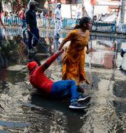 En demonstrant hjälper en annan demonstrant att ta sig upp efter att polisen använt vattenkanoner. Bikas Das / TT NYHETSBYRÅN