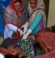 En skadad kvinna tas omhand efter bombdådet mot templet. Shakil Adil / TT NYHETSBYRÅN