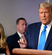 Donald Trump vid gårdagens pressträff. Pressekreteraren Kayleigh McEnany lyssnar. Evan Vucci / TT NYHETSBYRÅN