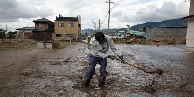 En person skyfflar lera efter tyfonens framfart Jae C. Hong / TT NYHETSBYRÅN