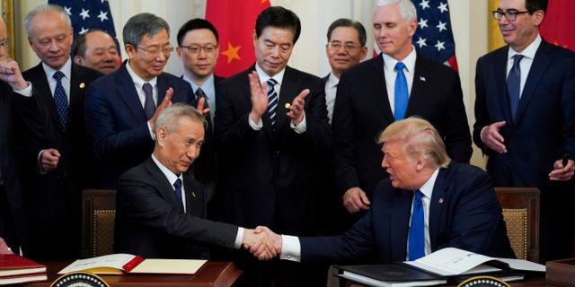 Kinas chefsförhandlare, vice premiärminister Liu He, skakar hand med USA:s president Donald Trump under avtalsceremonin i veckan. Kevin Lamarque / TT NYHETSBYRÅN