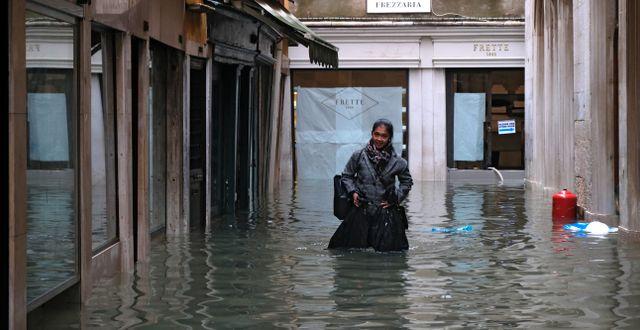 En kvinna vadar i Venedigs vatten. MANUEL SILVESTRI / TT NYHETSBYRÅN