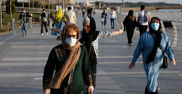 Människor med skyddsmasker i Iran. Vahid Salemi / TT NYHETSBYRÅN