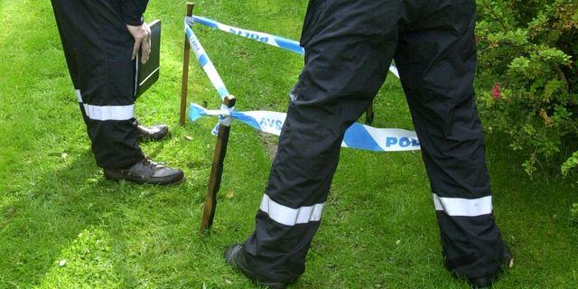 Arkivbild på två poliser som undersöker ett hjulspår på en gräsmatta. Claudio Bresciani/TT / TT NYHETSBYRÅN