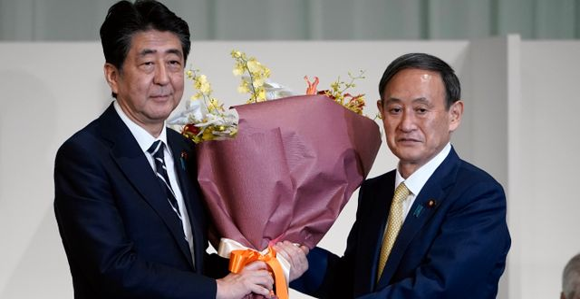 Shonzo Abe tar emot blommor från Yoshihide Suga Eugene Hoshiko / TT NYHETSBYRÅN