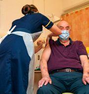Brian Pinker får Astras vaccin. Steve Parsons / TT NYHETSBYRÅN