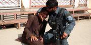 En afghansk polis tröstar en man som gråter efter attacken mot mödravårdskliniken. Rahmat Gul / TT NYHETSBYRÅN