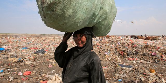 En kvinna bär en säck med återvinningsbara varor på en soptipp utanför al-Hudaydah, på en bild från i vintras.  ABDULJABBAR ZEYAD / TT NYHETSBYRÅN