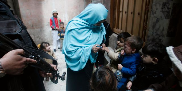Poliser vaktar hälsoarbetare som vaccinerar mot polio. Muhammad Sajjad / TT NYHETSBYRÅN
