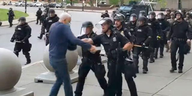 Poliserna knuffar den 75-åriga mannen så att han faller till marken.  Mike Desmond / TT NYHETSBYRÅN
