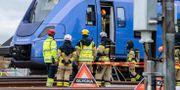 Polis, räddningstjänst och tågpersonal på plats vid det pågatåg som började brinna längst fram vid förarplatsen då det befann sig strax norr om stationen i Eslöv på måndagseftermiddagen. Johan Nilsson/TT / TT NYHETSBYRÅN
