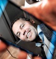 Huaweis nordenchef Kenneth Fredriksen som speglar sig i sin mobil.  Tomas Oneborg/SvD/TT / TT NYHETSBYRÅN