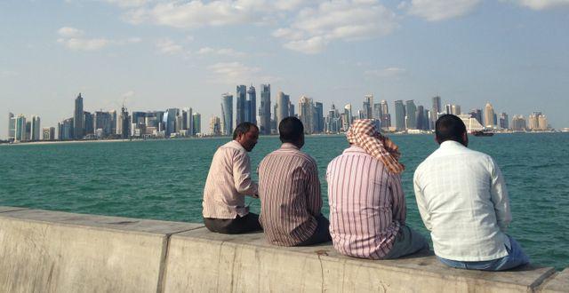 Arkivbild/Män sitter och tittar ut över Dohas stadssilhuett. Rob Harris / TT NYHETSBYRÅN