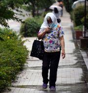 En äldre kvinna med ansiktsmask promenerar på en gata i Tokyo.  Eugene Hoshiko / TT NYHETSBYRÅN