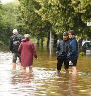 Personer vadade genom vattenmassor efter de kraftiga skyfall.  Fredrik Sandberg/TT / TT NYHETSBYRÅN