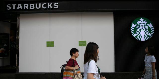 Kvinnor går förbi Starbucks i Kina. Mark Schiefelbein / TT NYHETSBYRÅN