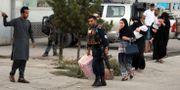 En ur den afghanska säkerhetsstyrkan lotsar en familj till säkerhet. Rahmat Gul / TT NYHETSBYRÅN/ NTB Scanpix
