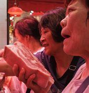 Kvinnor köper fläskkött på en kinesisk marknad.  Kin Cheung / TT NYHETSBYRÅN