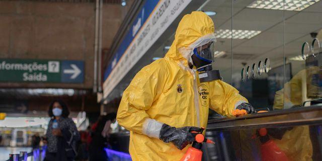 Person i skyddskläder rengör en bussterminal i Brasilien. Fotoarena / TT NYHETSBYRÅN