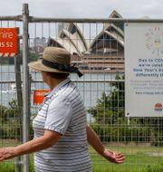 En kvinna vandrar förbi Operahuset i Sydney, som har spärrats av med stängsel. Mark Baker / TT NYHETSBYRÅN