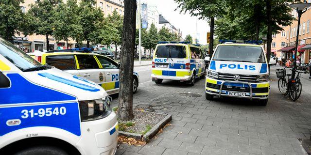 Polisbilar på plats utanför lägenheten där kvinnan hittades död. Karin Wesslén/TT / TT NYHETSBYRÅN