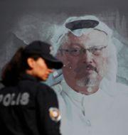 En turkisk polis framför en bild på den mördade journalisten Jamal Khashoggi.  Lefteris Pitarakis / TT NYHETSBYRÅN