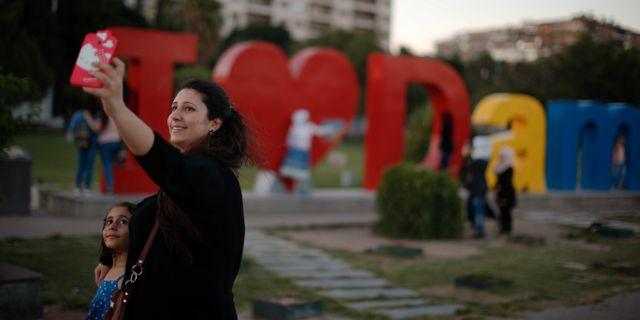 """En syrisk kvinna med sitt barn tar en selfie framför en """"I love Damascus""""-konstverk på Omayyidtorget i huvudstaden. Hassan Ammar / TT NYHETSBYRÅN/ NTB Scanpix"""