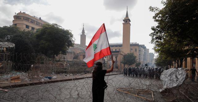 En kvinna syns med Libanons flagga under demonstrationer i Beirut.  Hassan Ammar / TT NYHETSBYRÅN