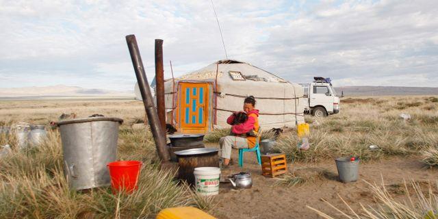 En kvinna framför en jurta på den mongolska stäppen. Petr David Josek / SCANPIX