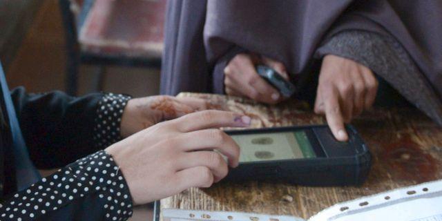 En kvinnlig väljare får sitt finger skannat under dagens val. STR / TT NYHETSBYRÅN/ NTB Scanpix