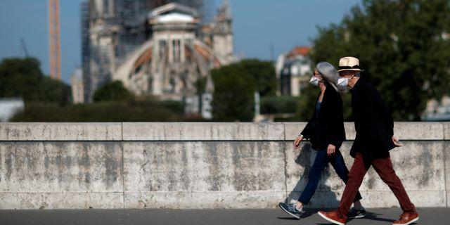 Två personer med munskydd passerar förbi Notre-Dame-katedralen i Paris under måndagen den  27 april. GONZALO FUENTES / TT NYHETSBYRÅN
