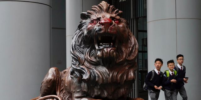 Studenter passerar förbi ett av de vandaliserade lejonen.  Vincent Yu / TT NYHETSBYRÅN