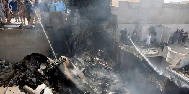 Människor försöker släcka elden från det kraschade planet i Karachi.  Fareed Khan / TT NYHETSBYRÅN