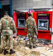 Soldater tittar på en förstörd bankomat i Soweto, Johannesburg.  Ali Greeff / TT NYHETSBYRÅN