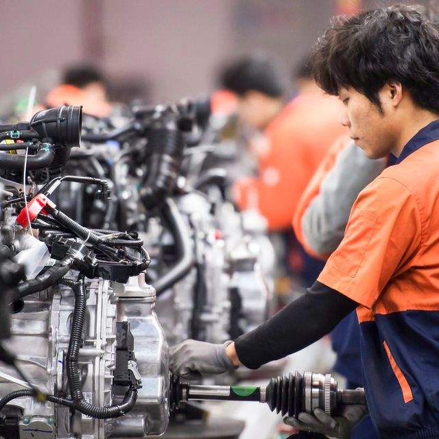 March 14, 2017, Linhai, Zhejiang Province, China, Geely Automobile Manufacturing Plant, assembly plant workers are assembling the engine, representing the highest level of China's state-owned car bran shutterstock