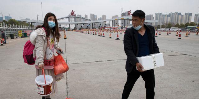 Människor på väg till en hälsokontroll innan de får återvända till sina jobb.  Ng Han Guan / TT NYHETSBYRÅN