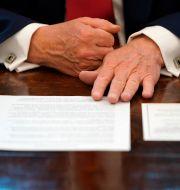 Donald Trump har avtalet framför sina händer.  Alex Brandon / TT NYHETSBYRÅN