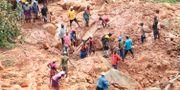 En familj letar efter sin son som begravdes i leran. Tsvangirayi Mukwazhi / TT NYHETSBYRÅN/ NTB Scanpix
