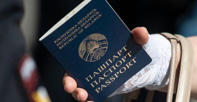 En kvinna håller i ett belarusiskt pass.  Pavel Golovkin / TT NYHETSBYRÅN