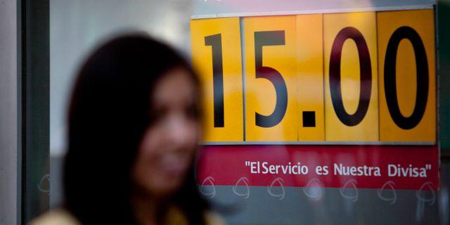 Kvinna går förbi skylt med växelkurs för mexikanska peson. Gregory Bull / TT NYHETSBYRÅN