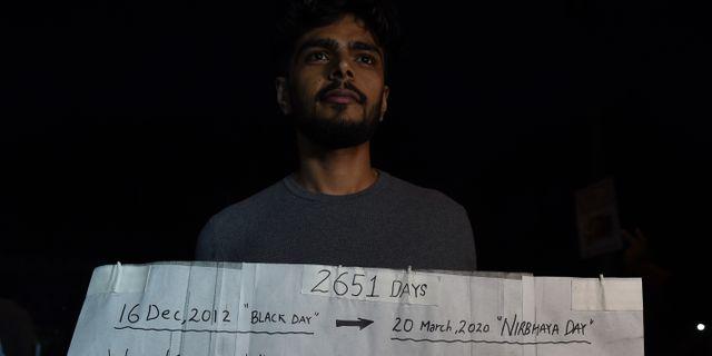 En man håller upp en skylt där han uppmanar sina medmänniskor att stanna hemma så att de inte sprider coronaviruset. Bilden är tagen i New Delhi.   MONEY SHARMA / TT NYHETSBYRÅN
