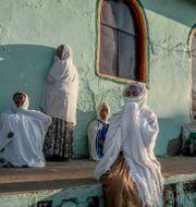 Kvinnor som flytt från Tigray står utanför en kyrka i Qadarif i östra Sudan.  Nariman El-Mofty / TT NYHETSBYRÅN