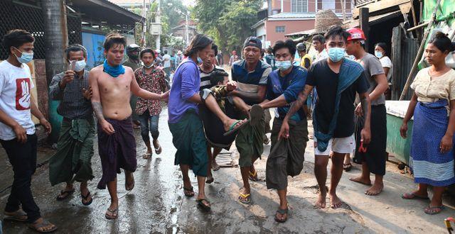 Skadad man bärs bort efter att ha skjutits under lördagens protester. TT NYHETSBYRÅN