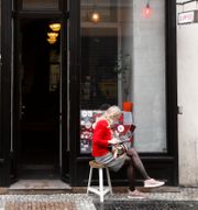 Kvinna sitter med sin dator utanför ett kafé i Prag.  Petr David Josek / TT NYHETSBYRÅN