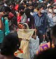 Människor köar för att gå på ett tåg i delstaten Maharashtra i Indien.  Rafiq Maqbool / TT NYHETSBYRÅN