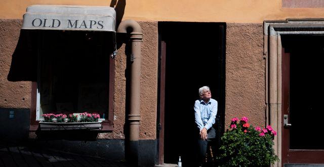 En man sitter i solen utanför en butik i Gamla stan i Stockholm.  Ali Lorestani/TT / TT NYHETSBYRÅN