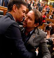 Pedro Sánchez omfamnas av Unidas Podemos-ledaren Pablo Iglesias PIERRE-PHILIPPE MARCOU / AFP