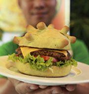 """Restaurangägaren Hoang Tung håller upp en """"coronaburgare"""" i Hanoi, Vietnam.  Hau Dinh/TT"""