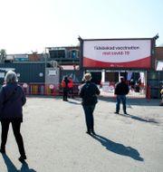 Människor väntar i kö inför vaccinering i klubblokalen Fållan i Stockholm.  Jessica Gow / TT NYHETSBYRÅN