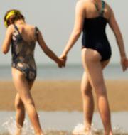 Två personer går på stranden i belgiska staden De Haan. Francisco Seco / TT NYHETSBYRÅN/ NTB Scanpix